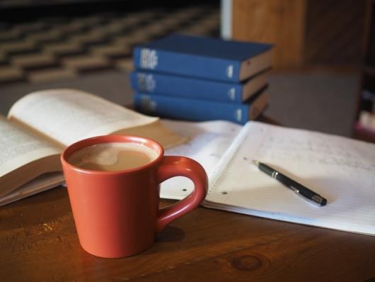 ノートとコーヒーが机の上に置かれている