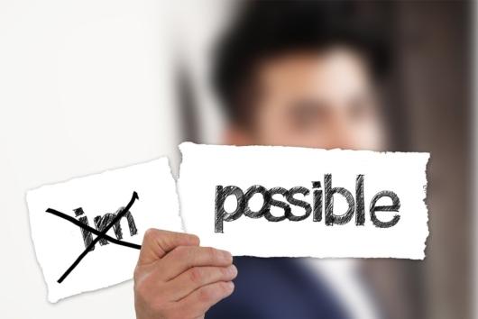 「possible」と書かれた紙を持っている男性