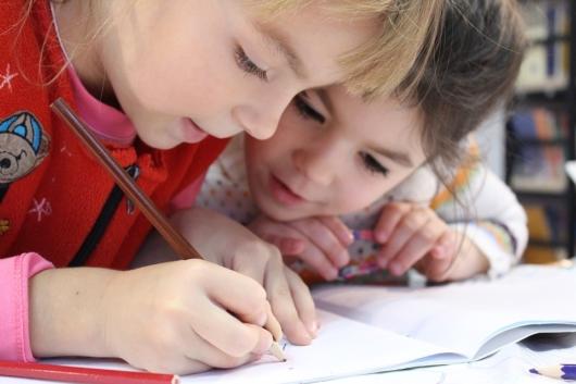 寄り添ってノートを見ている子供2人