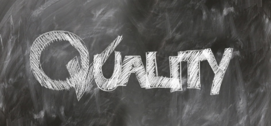 黒板に白い「Quality」の文字