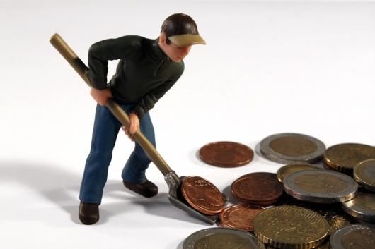 お金をシャベルで掬っている男性