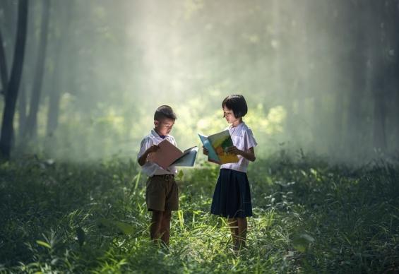 森の中で本を読む男の子と女の子