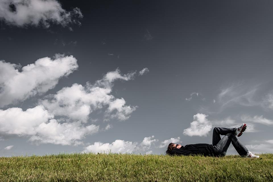 青空の元で寝転がっている男性